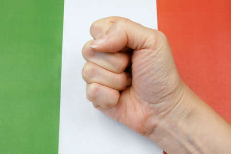clenched fist against the background of the Italian flag, protests in Italy, closeup