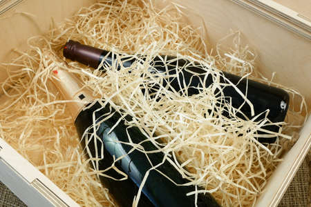 bottle of expensive elite wine in a wooden box with shavings, online order and delivery wine, internet wine shops, closeup Imagens