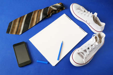 white sneakers, tie, mobile phone and empty white sheet for copy space on blue background, dad's day concept, top view