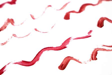 Liquid lipstick on white background, red liquid lipstick with a single color swipe, closeup