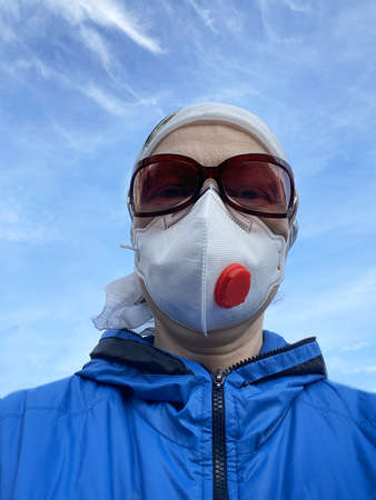 woman in high level protection respirator ffp3 and glasses on blue sky background, outdoors, virus concept