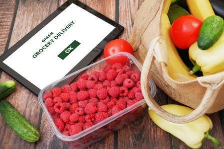 Organic Vegetables and fruits in cotton bag and tablet pc, online market, green grocery delivery at home concept, buy online concept Imagens