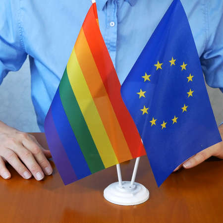rainbow lgbt flag and European Union flag. Homosexual marriage. Same-sex marriage is allowed in european countries Concept. Closeup