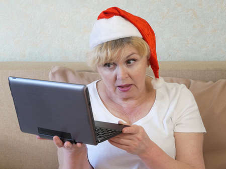 senior woman in santa claus red hat with xmas deocration congratulates with new year with laptop, merry christmas and happy new year concept Imagens