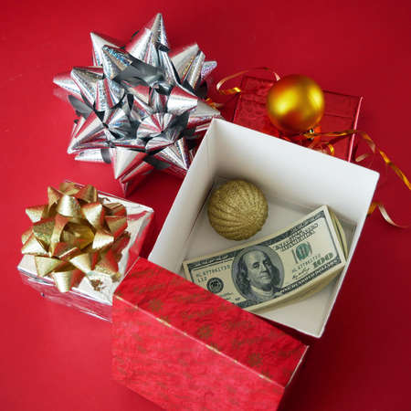 big gift box with ribbon bow and stack of money, merry chirtmas and happy new year concept
