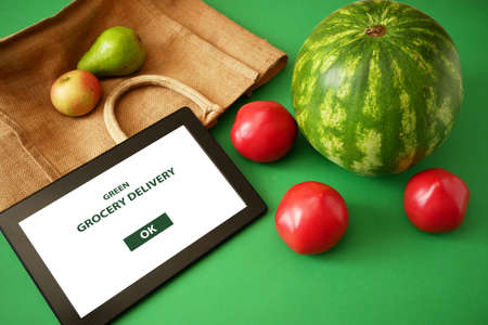 Organic Vegetables and fruits in cotton bag and tablet pc, online market, green grocery delivery at home concept
