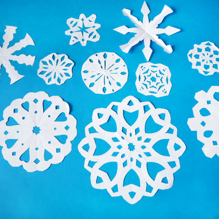 snowflakes paper crafts, handmade new year decoration on blue background, xmas mood, closeup