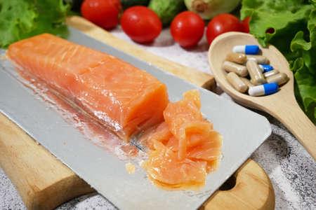 healthy food (vegetables, fish, fruits) vs pills concept, closeup