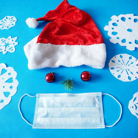fanny face from santa claus red hat, xmas balls as eyes, new year tree branch as nose and medical face mask and paper snowflakes, wealth and health in new year, closeup