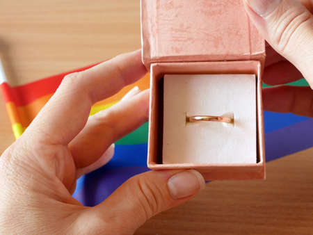 gold wedding ring on rainbow lgbt flag and European Union flag. Homosexual marriage. Same-sex marriage is allowed in european countries Concept. Closeup Imagens