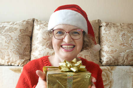 Woman with gifts for Christmas and New Year at home, smiling woman in santa helper hat with gift box, concept