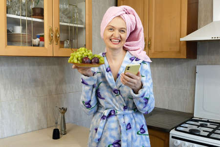 happy woman in bath towel on her head and wearing bathrobe holding a plate with grapes and plums in kitchen at home, healthy food concept