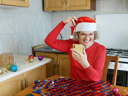 woman speaks on a mobile phone and wishes a happy new year to relatives and friends. at home in kitchen, smiling woman in santa helper hat with gift box, concept