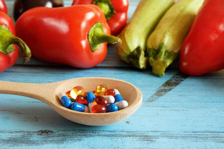 Fruit and pills, vitamin supplements with on wooden background. Healthy lifestyle, diet concept, closeup