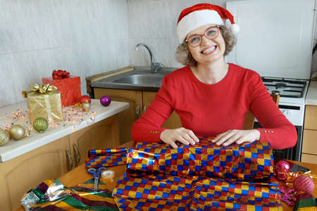 Woman preparing gifts for Christmas and New Year at home in kitchen, smiling woman in santa helper hat with gift box, concept