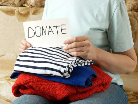 Woman fold clothes Washed Laundry And Clothes, Clothes for donation, closeup Imagens