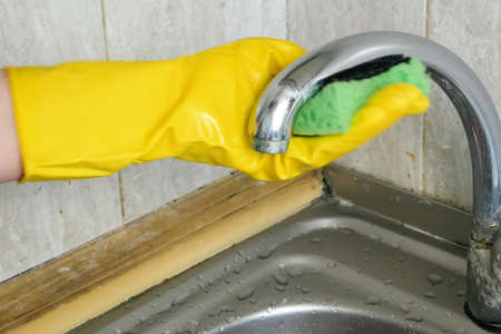 Cleaning home table, sanitizing kitchen table surface with disinfectant spray bottle washing surfaces with sponge and gloves. Closeup