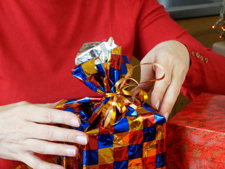 Woman preparing gifts for Christmas and New Year at home with gift box, concept Imagens
