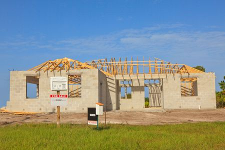 residential construction: New Home Construction Cement Block walls, wood truss roof viewed from front with for sale sign
