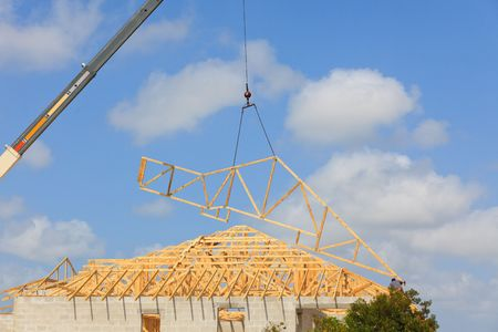 Roof Truss hanging from a crane being installed onto a new roof. Blue sky with clouds in background. Archivio Fotografico