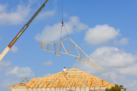 Roof Truss hanging from a crane being installed onto a new roof. Blue sky with clouds in background. photo