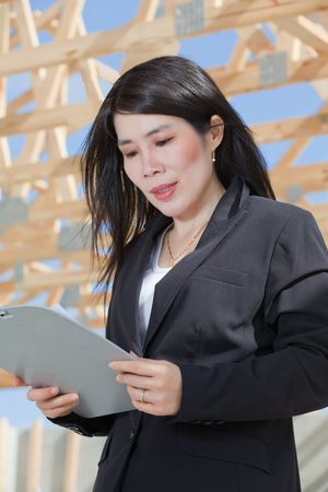 Asian Woman Contractor looking at clipboard photo