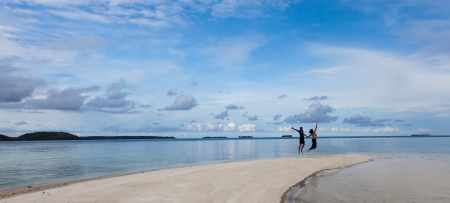 Couple Jumping in Air on Remote Indoneisan Beach