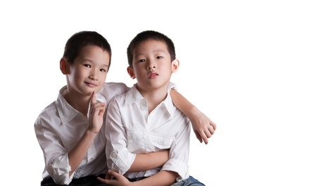 kids hugging: Two Young Asian Brothers wearing white shirts on an Isolated white background