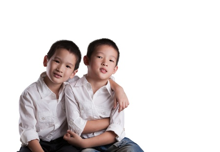 Twee Jonge Aziatische Brothers dragen witte shirts op een witte achtergrond