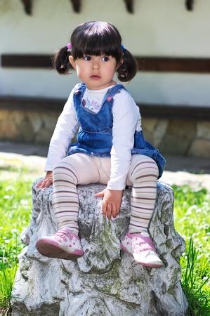 Kleine Mädchen sitzen im Garten