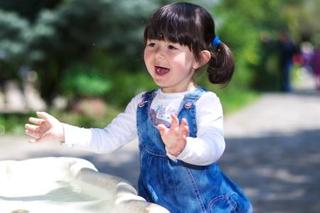 Kleines Mädchen mit Wasser spielen und lachen