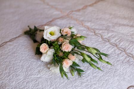 wedding bouquet: Wedding bouquet lies on a bed