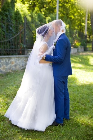femme romantique: Beautiful bride hugs and kisses on the cheek in nature Banque d'images