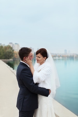 tenderly: groom tenderly embraced the bride on the sea promenade Stock Photo