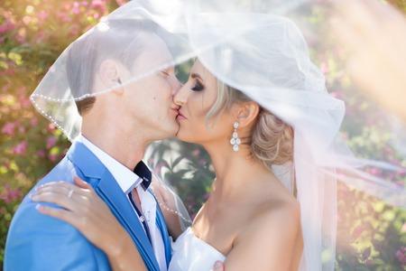 femme romantique: Le mari� embrasse doucement la mari�e sur un jour d'�t�