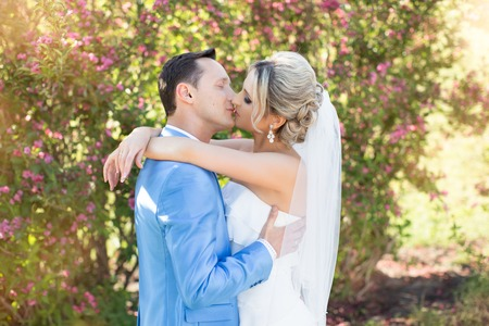 cute lady: The groom gently kisses the bride on a summer day
