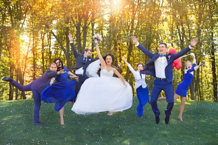 Newlyweds having fun with the guests in a meadow in the park