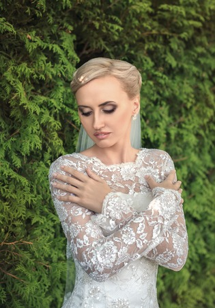 bridal gown: Beauty bride in bridal gown with bouquet and lace veil on the nature.