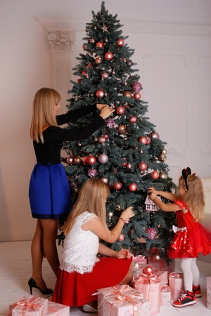 decorate: Happy mother and daughter decorates the Christmas tree
