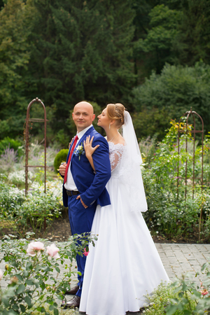 moment: Bride gently pressed her to the groom on the background of nature