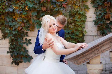 gently: The groom gently hug the brides shoulders at wedding walk