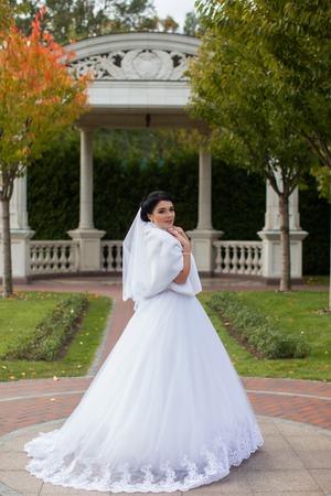 Bride on promenade in summer park posing on photo