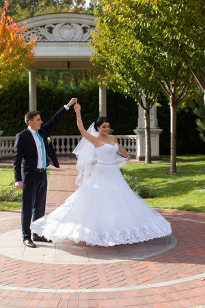 A happy bride swirls for the groom in the summer park on the mall