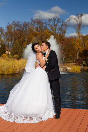 The groom tenderly kisses the happy bride in the neck standing on the pier Banque d'images