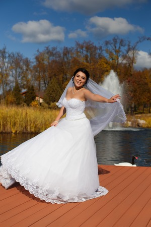 A happy bride in a rich wedding dress is standing on the pier