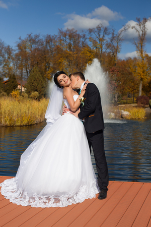 The groom tenderly kisses the happy bride in the neck standing on the pier Standard-Bild