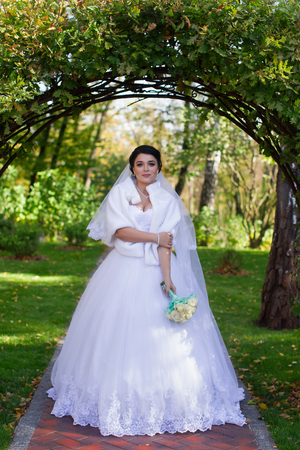 A stylish bride with a bouquet in her hands is standing under a green arch