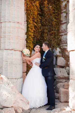 The groom tenderly embraced the happy bride standing at the column