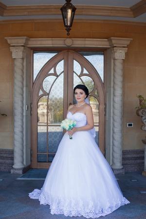 Bride with bouquet on retro door background Banque d'images