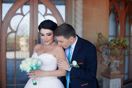 The groom tenderly kisses the bride's shoulder against the retro-door background